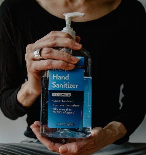 hands holding bottle of hand sanitizer